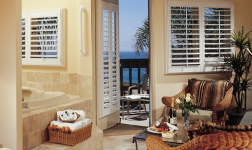 Plantation shutters on casement windows in a lakefront condo.